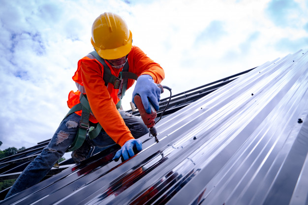 roofer-working-roof-structure-building-construction-site-roofer-using-air-pneumatic-nail-gun-installing-metal-sheet-top-new-roof_64073-73